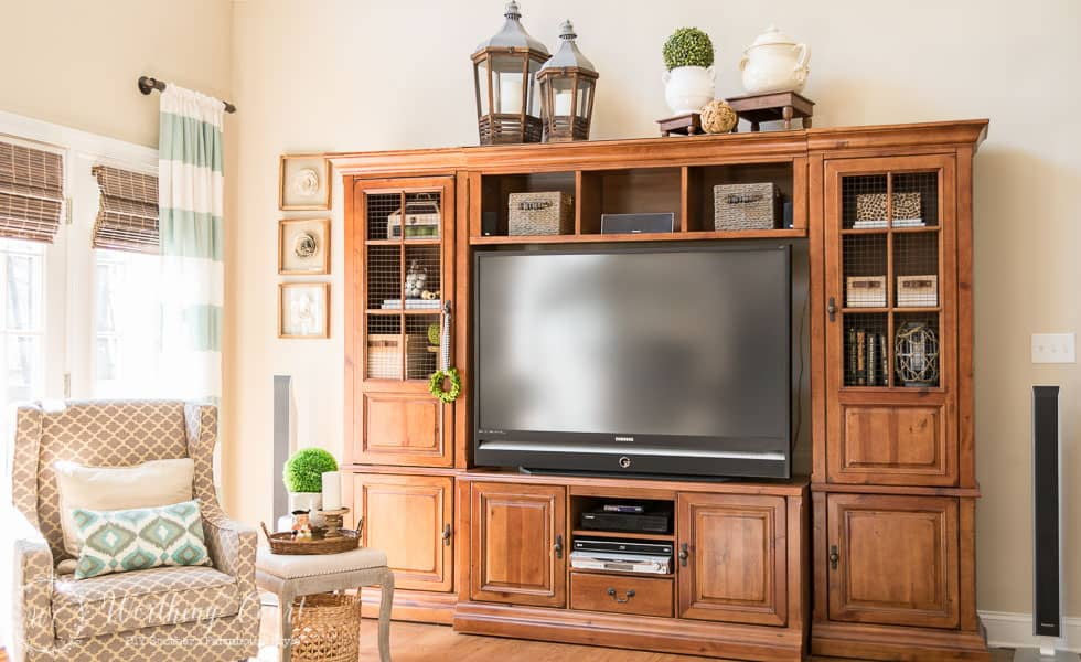 The before and after of this family room is amazing. It was taken from dark and dated to light and bright filled with rustic farmhouse touches, which includes a rustic entertainment center.