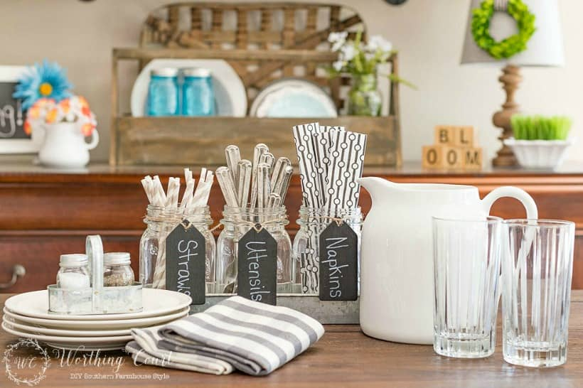 There are plates cups and mason jars filled with utensils.