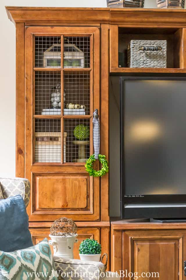 The before and after of this family room is amazing. It was taken from dark and dated to light and bright filled with rustic farmhouse touches, which includes a rustic entertainment center where the glass in the doors was replaced with cage wire.