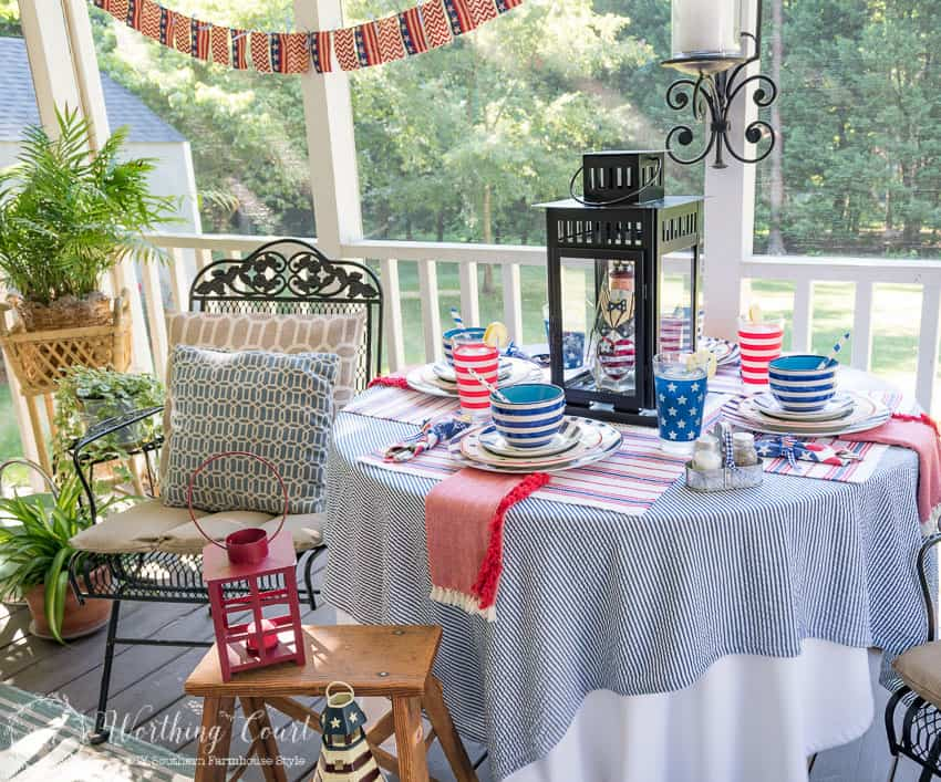 A patriotic table setting on a farmhouse porch filled with loads of red, white and blue vintage Americana patriotic decorating ideas for Memorial Day, Flag Day and July 4th.