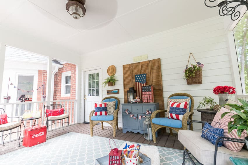 A farmhouse porch filled with loads of red, white and blue vintage Americana patriotic decorating ideas for Memorial Day, Flag Day and July 4th.