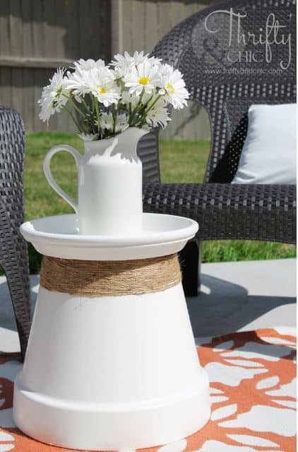 Dress up a large terra cotta pot and its drainage tray with some spray paint and twine for an inexpensive outdoor table.