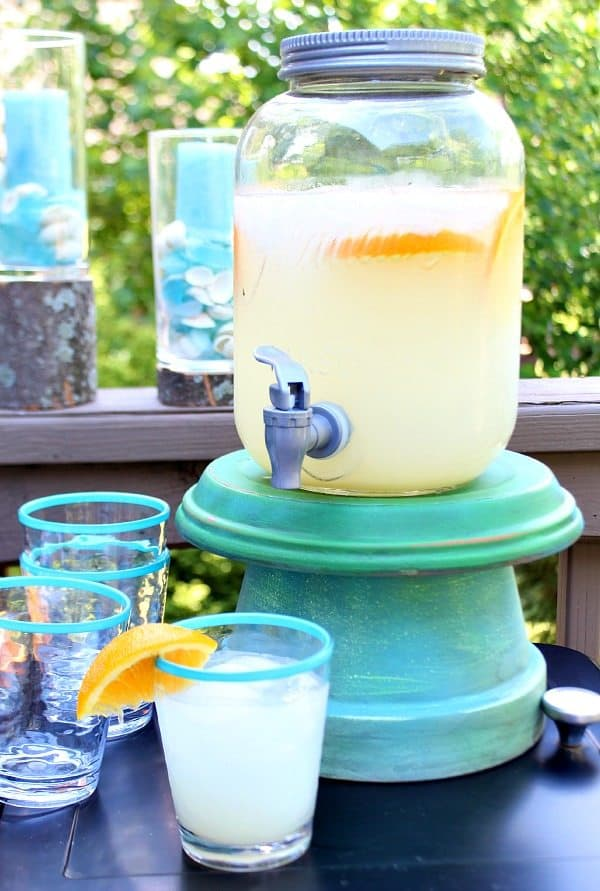 DIY drink dispenser stand with glasses of lemonade in front of it.