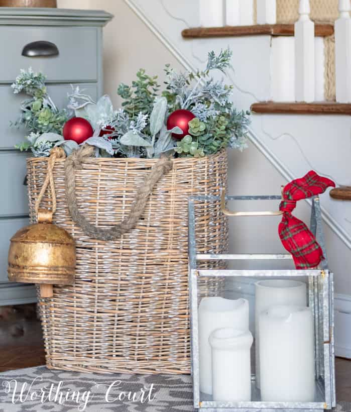 basket fill with greenery and red Christmas ornaments