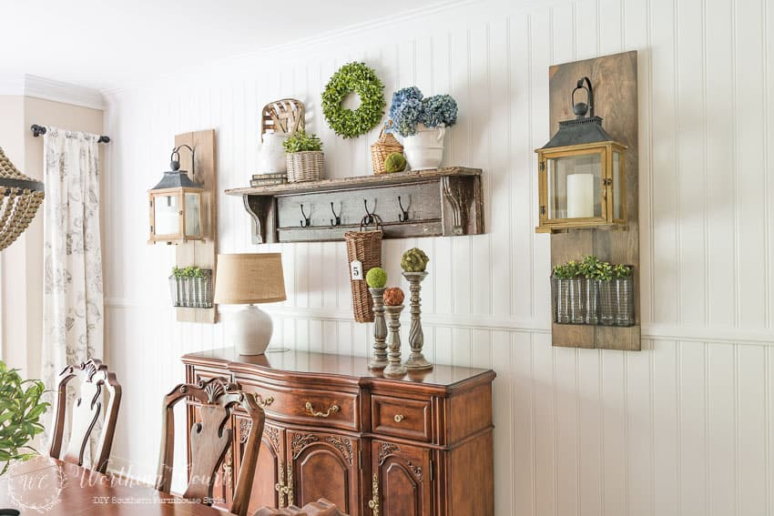 DIY farmhouse style planked shiplap wall with a vintage mantel shelf, buffet and Fixer Upper style wall lanterns