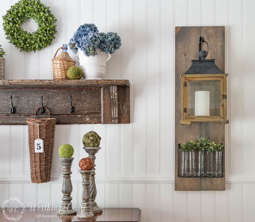 DIY farmhouse style hanging lantern and wire basket filled with vases and sprigs of greenery