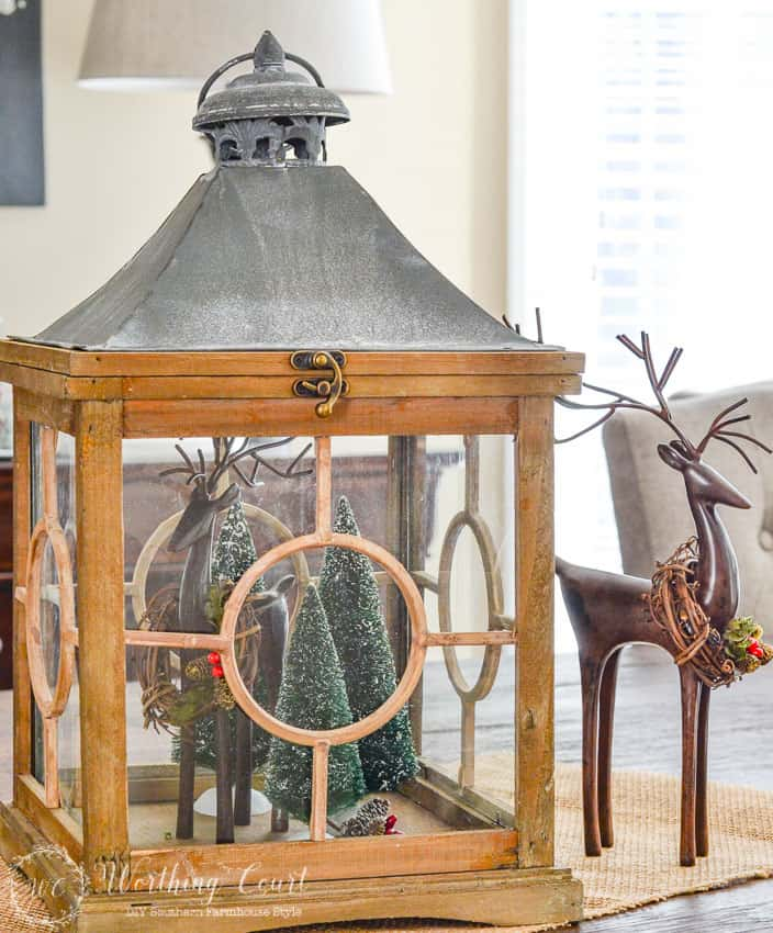 how to decorate with lanterns fill a lantern with mini christmas trees and small deer