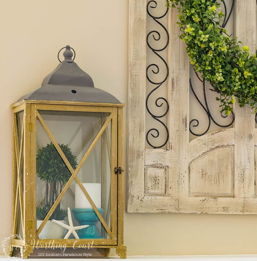 How To Decorate With Lanterns - fill a large lantern with a topiary, white candle and a single starfish for a summer look