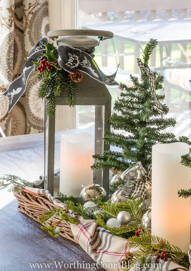 Christmas centerpiece in a wicker tray with lanterns, candles and mini tree
