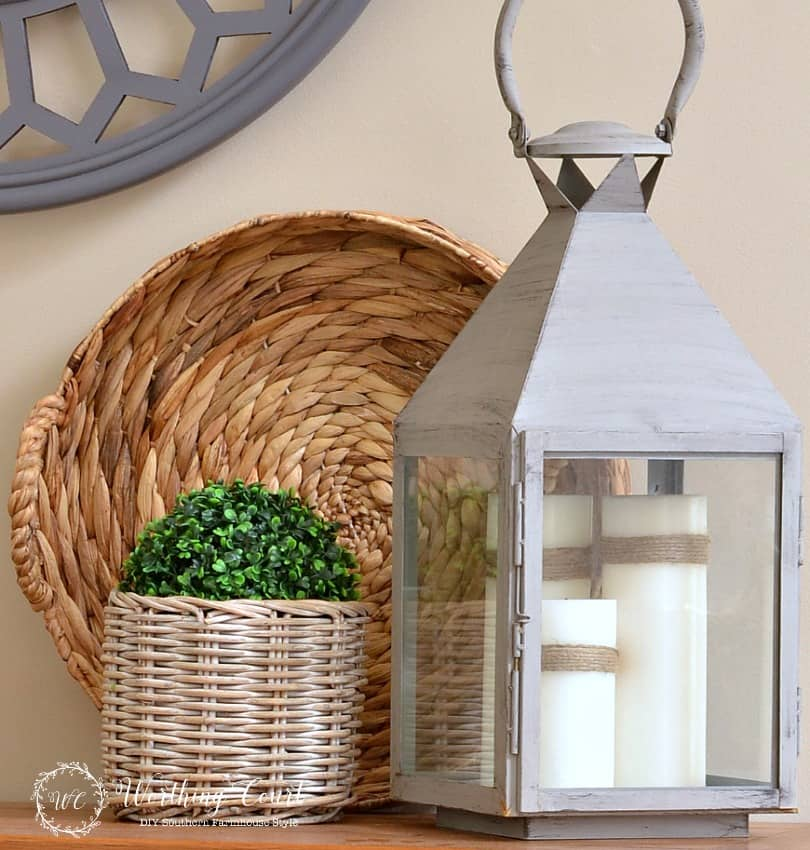 large gray lantern filled with a trio of white candles