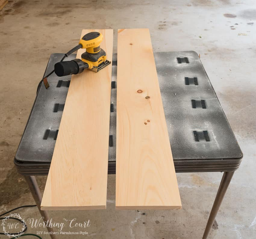 Using a sander on the wooden planks.
