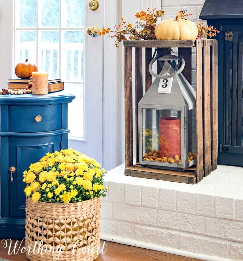 Fall decor on a white brick fireplace hearth