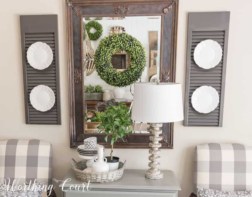 Farmhouse Dining Room Makeover - a mirror in a dark room adds a bit of light and relfect the pretty vignette across from it
