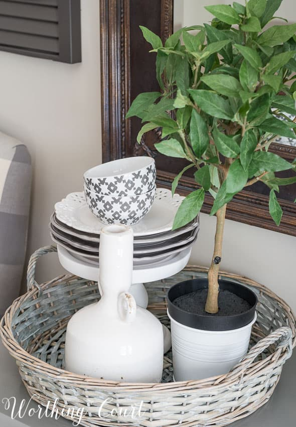Farmhouse Dining Room Makeover - vignette with stacked dishes on a pedestal inside a round wicker tray