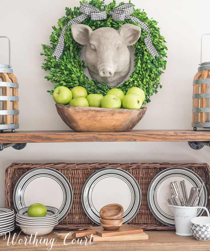 Faux pig head wall hanging above open rustic farmhouse shelves