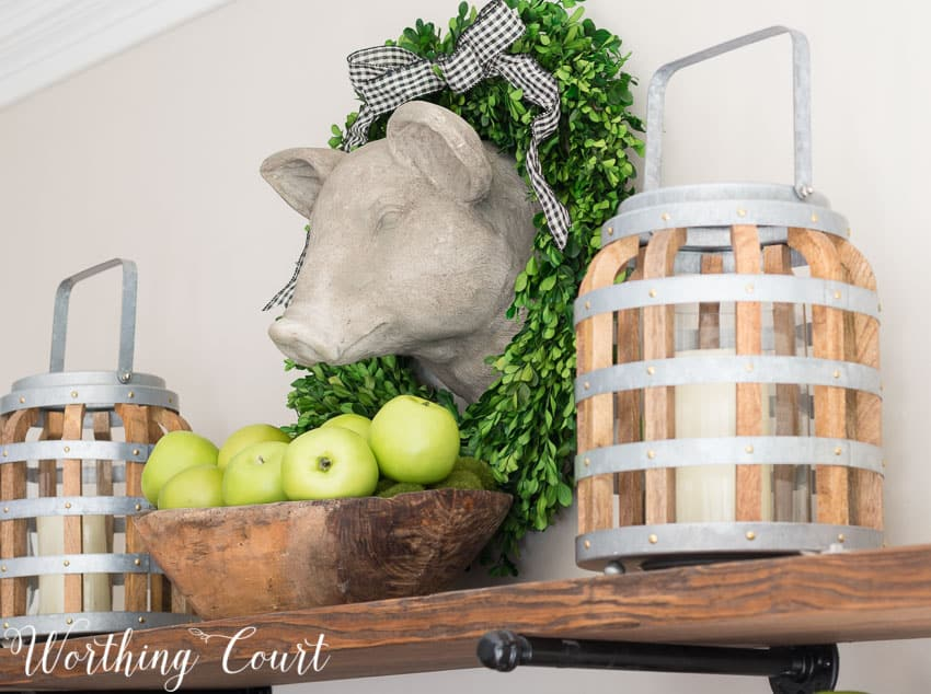 A faux pig head, surrounded by a preserved boxwood wreath, hangs above open rustic farmhouse kitchen shelves