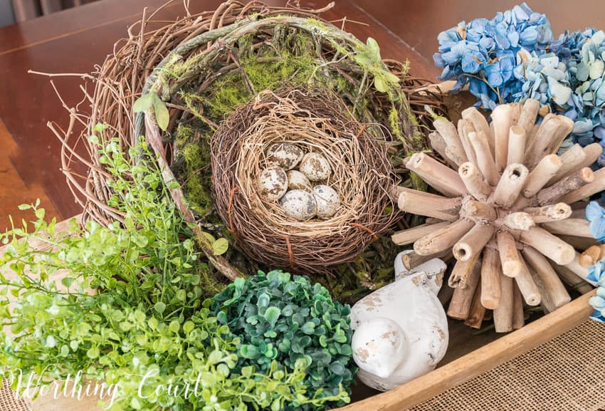 Wood dough bowl filled with spring decor such a small birds nest with faux eggs.