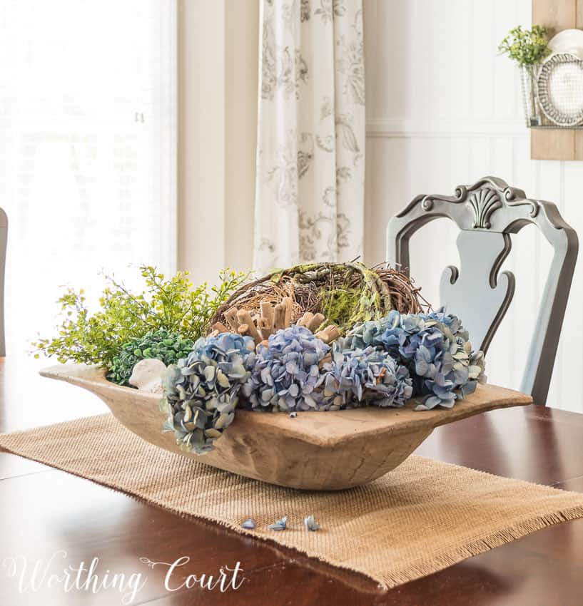 Large wooden dough bowl centerpiece filled with spring decor on the dining room table.