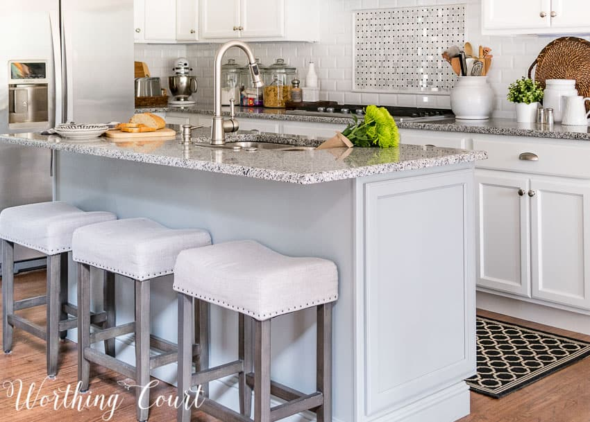 Gray island with white kitchen cabinets