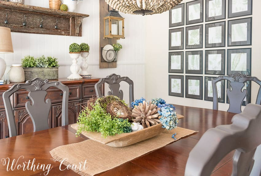 Wooden dough bowl filled with spring decor in the dining room.