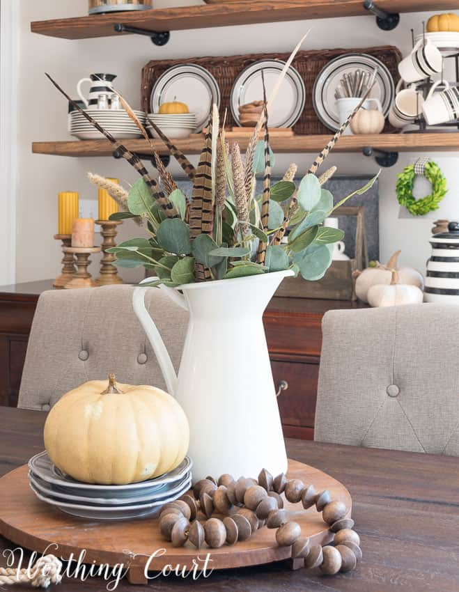 A white pitcher is filled with eucalyptus leaves, feathers and it is on a wooden tray that is round on the table.