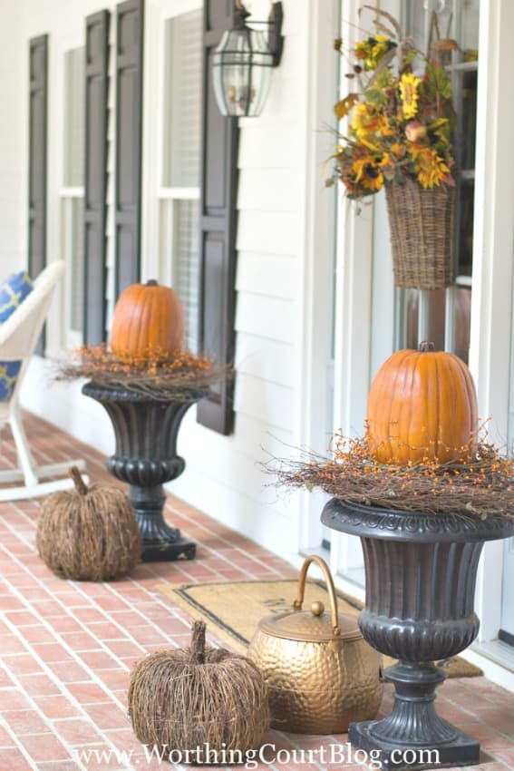 Easy fall front porch with two urns and pumpkins on them.