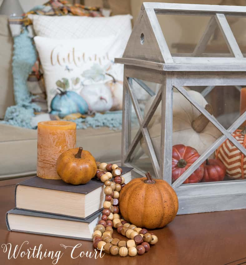 Fall coffee table with a terrarium, stacked books, bead strands and pumpkins || Worthing Court