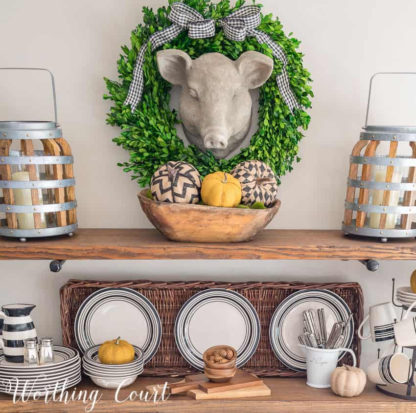 Herbert the pig has a wreath with a checkered bow around him and a dough bowl filled with fall items underneath on the shelves.
