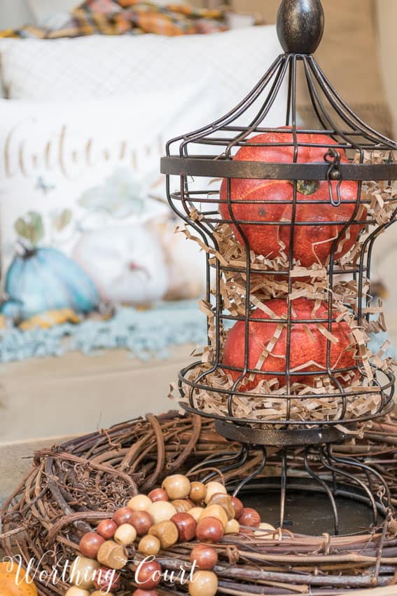 Fill a metal cage with pumpkins and brown paper filler for an easy fall display