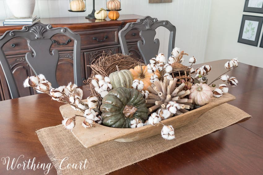 Dough bowl filled with fall goodies - a grapevine wreath, artificial pumpkins and cotton stems || Worthing Court