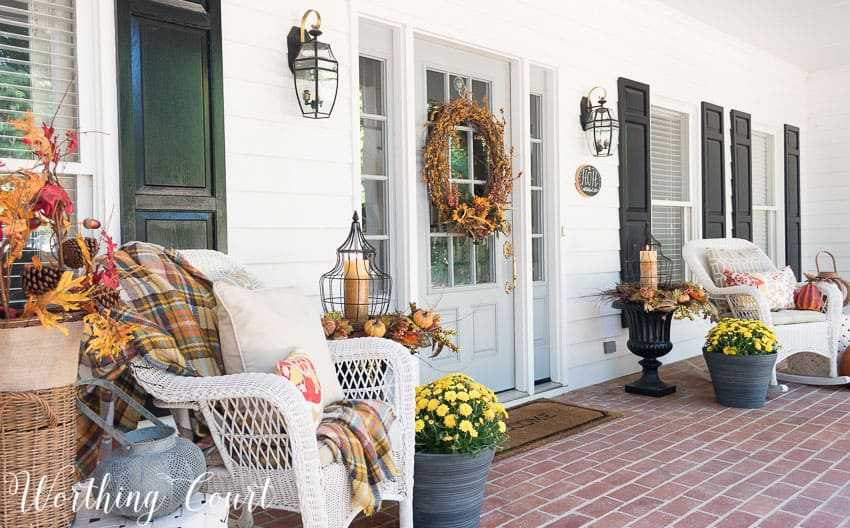 Farmhouse style fall front porch with wicker rockers and fall urns || Worthing Court
