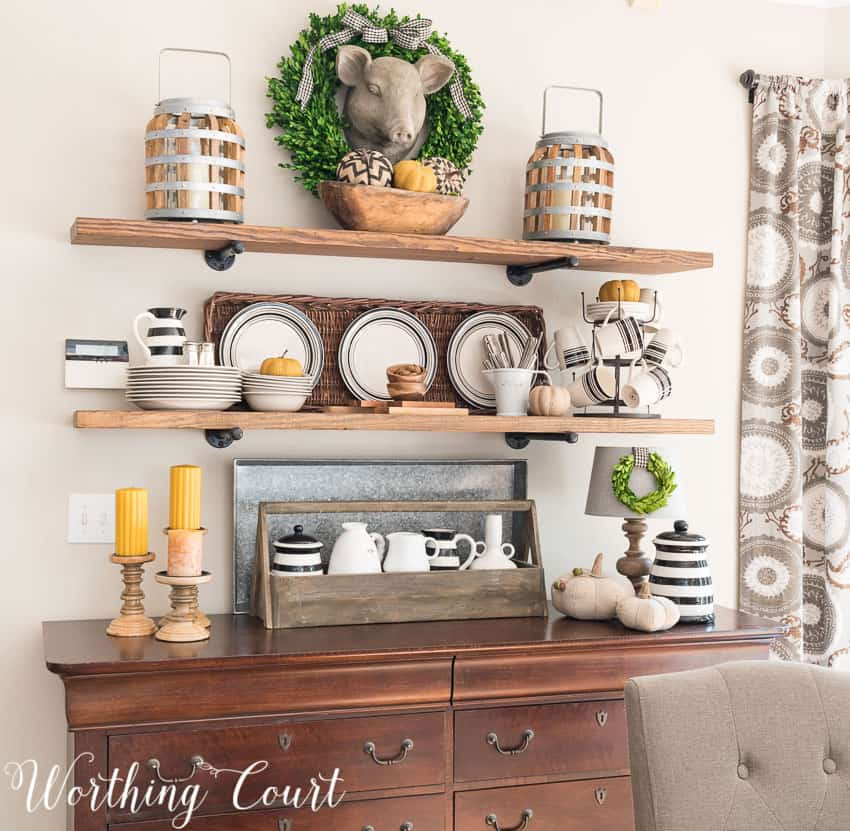 Farmhouse breakfast area open shelves decorated for fall above the wooden hutch.