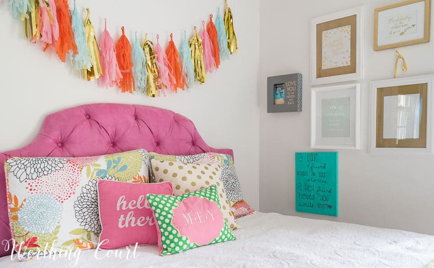 Pink upholstered headboard and a colorful tissue paper garland || Worthing Court