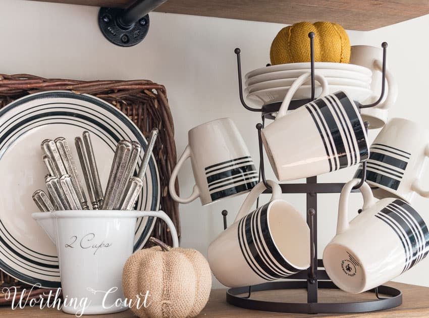 There is a orange fabric pumpkin on plates and a neutral fabric pumpkin beside the cups on the shelving unit.