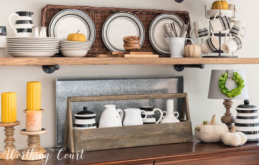 The rustic shelves have a wooden toolbox, black and white striped dishes and pitcher and also yellow candles.