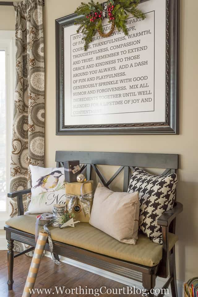 A small sitting bench with farmhouse pillows and a wreath on a picture frame above on the wall.