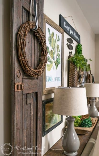 A rustic farmhouse texture filled gallery wall with a door on the wall and twig wreath on it.