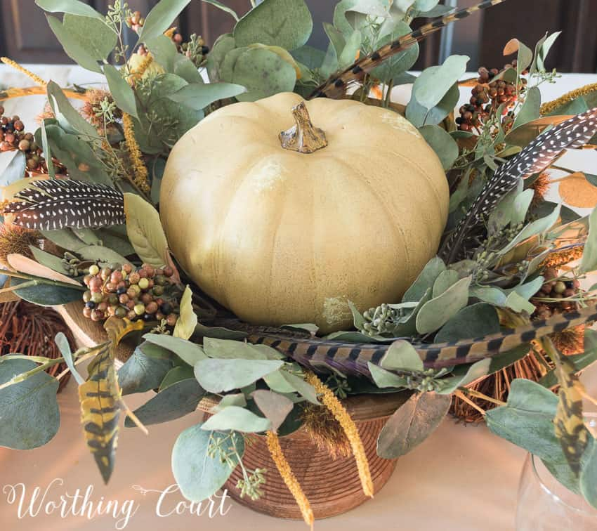 Thanksgiving centerpiece in a wooden pedestal bowl using a faux pumpkin, eucalyptus leaves and feathers || Worthing Court