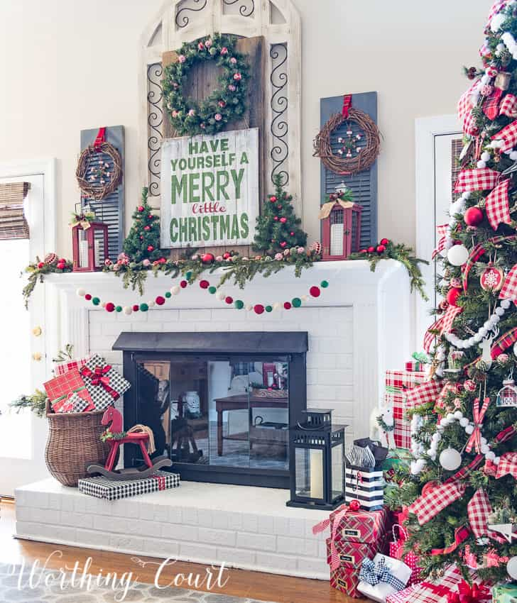 Farmhouse Christmas mantel decorated with traditional red and green with a large decorated Christmas tree beside it.