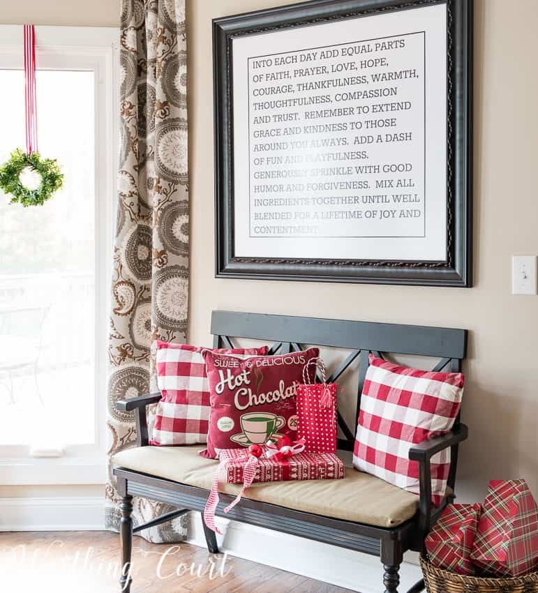 Bench with Christmas pillows in red and white checkered pattern.