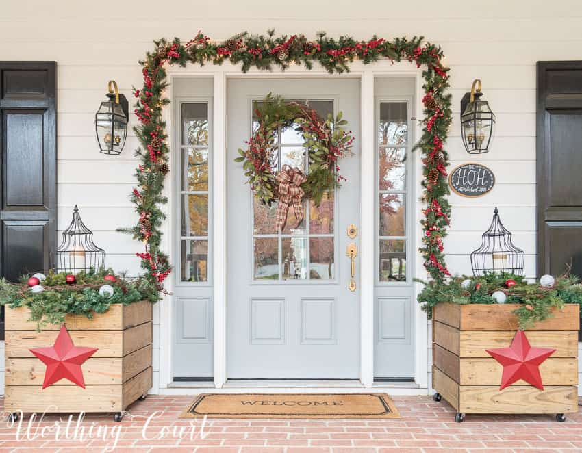 Front door surrounded with lighted garland and flanked with diy planters for Christmas || Worthing Court