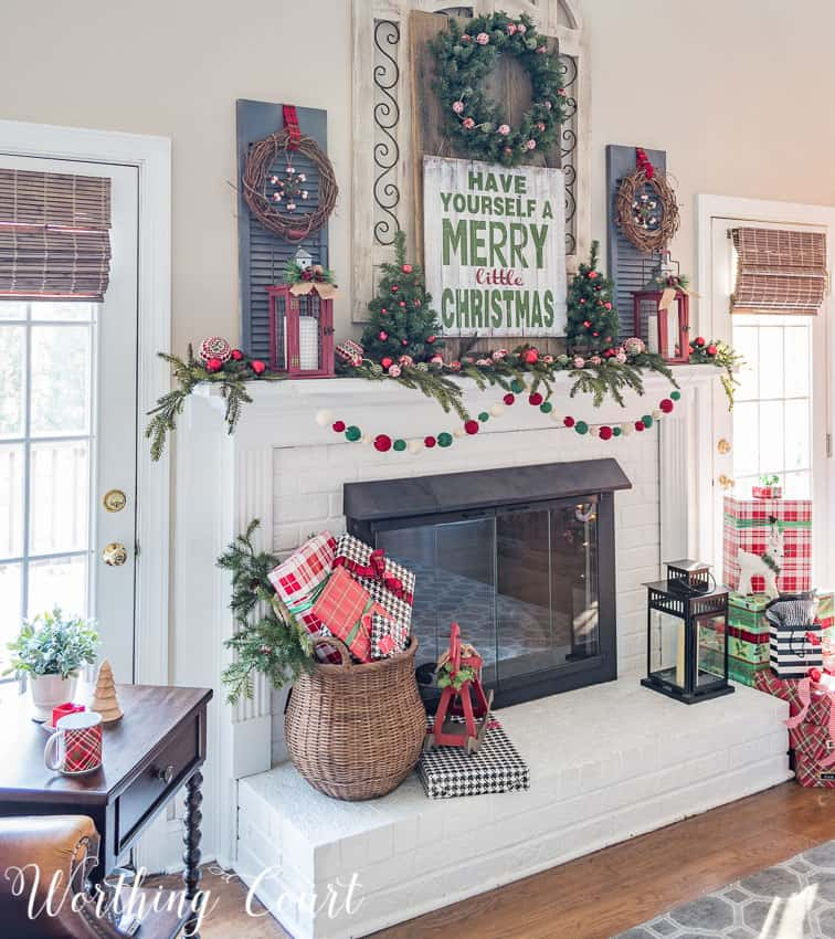 There is a large wicker basket filled with presents on the white fireplace mantel.