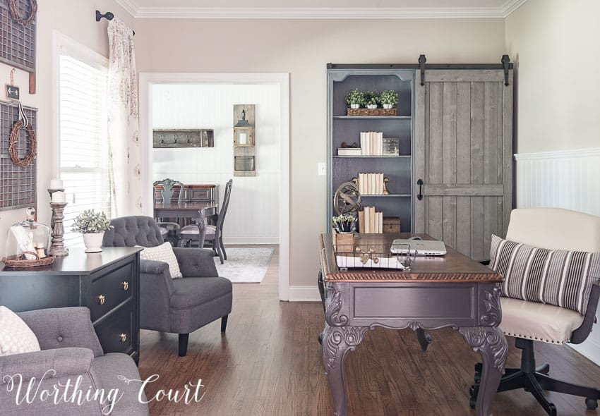 A home office with a grey desk and fabric chair, and a farmhouse style bookcase.
