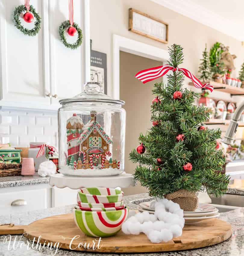 Kitchen island Christmas vignette with a house in a small glass canister || Worthing Court