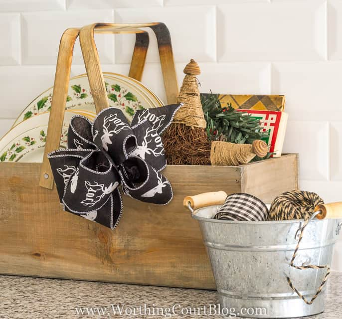 Fill a wooden box or a basket with an assortment of Christmas plates, a special cookbook, a large ornament and add a festive bow for an easy kitchen vignette || Worthing Court