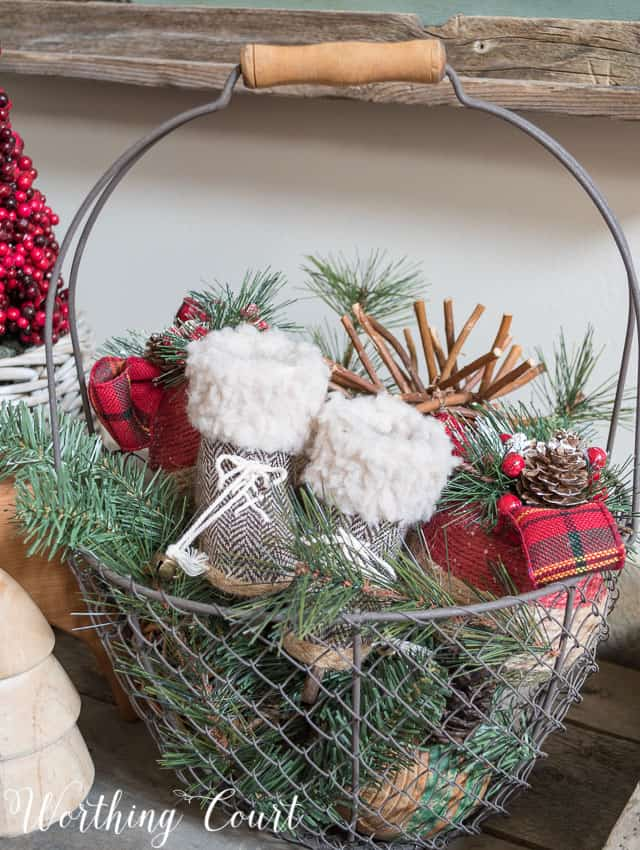 A wire metal basket filled with baby booties and pine cones.
