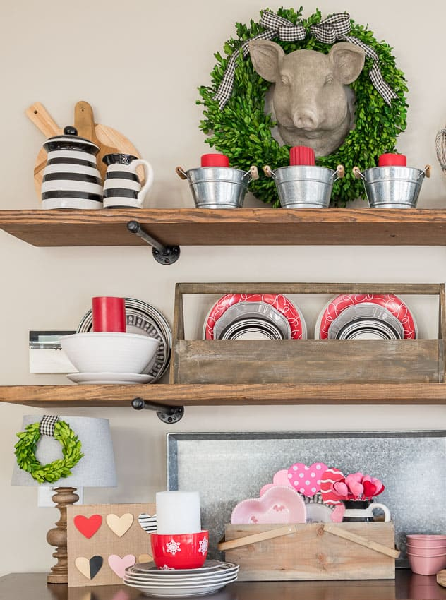 A wooden crate is on the sideboard with pink and red plates.