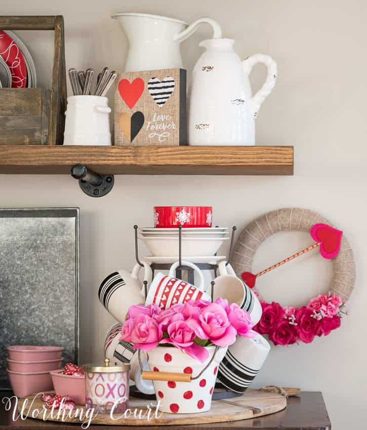 A small Valentine's Day wreath is on the wall beside the open shelves.