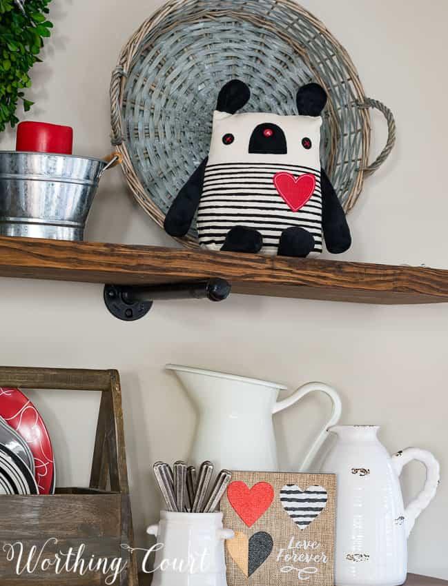 A little stuffed animal is on the open shelf.
