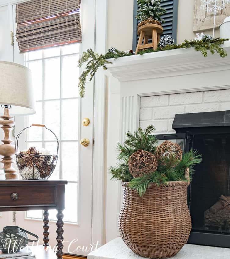 Wicker basket filled with artificial greenery and grapevine orbs for winter